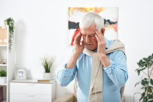 elderly man holding his head due to migraines