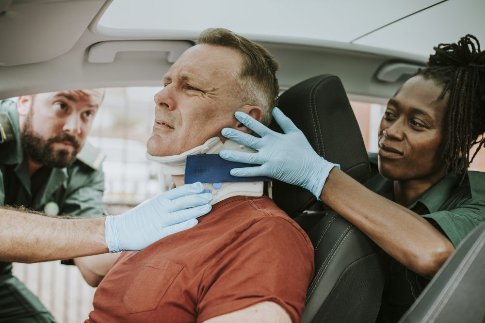 Paramedic placing a cervical collar to an injured man from car accident