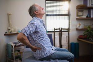 Elderly man having hip and lower back pain