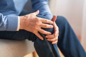 senior man holding his knee due to pain